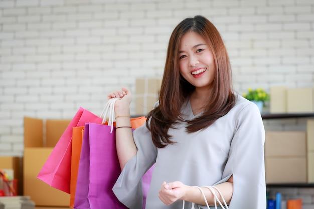 Femme heureuse avec ses sacs à provisions.