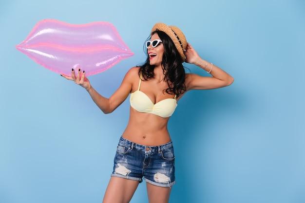 Femme heureuse en short en jean tenant des lèvres gonflables