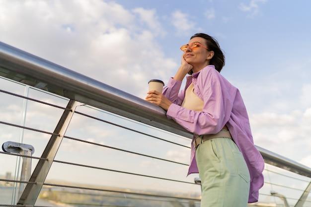 Femme heureuse avec une silhouette parfaite dans une chemise surdimensionnée violette élégante, appréciant une tasse de café tout en marchant sur un pont moderne