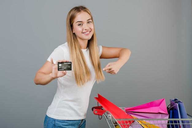 Femme heureuse souriante avec carte de crédit et chariot à paniers avec des sacs colorés, isolée sur fond gris