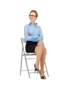 Femme heureuse et souriante sur une chaise dans les spécifications