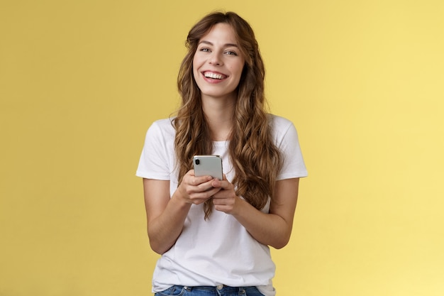 Femme heureuse souriante et enthousiaste animée utilisant un ami de messagerie sms sur smartphone vérifiant le flux des médias sociaux en naviguant sur internet tenir un téléphone portable en riant joyeusement sur fond jaune.