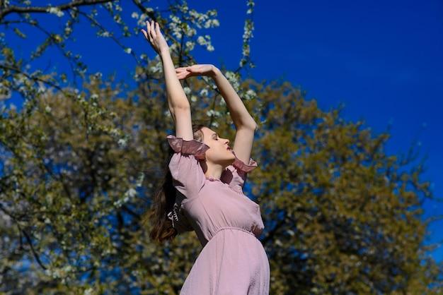 Femme heureuse souriante joyeuse avec les bras levés dansant en été pendant les vacances de voyage