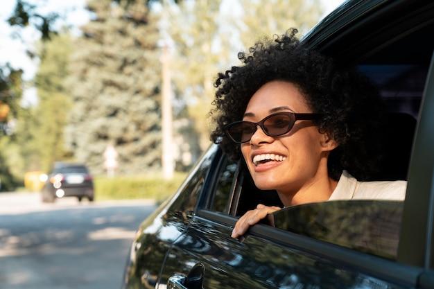 Femme heureuse souriante avec des lunettes de soleil dans une voiture