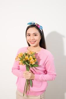Femme heureuse souriante à pleines dents tenant une fleur