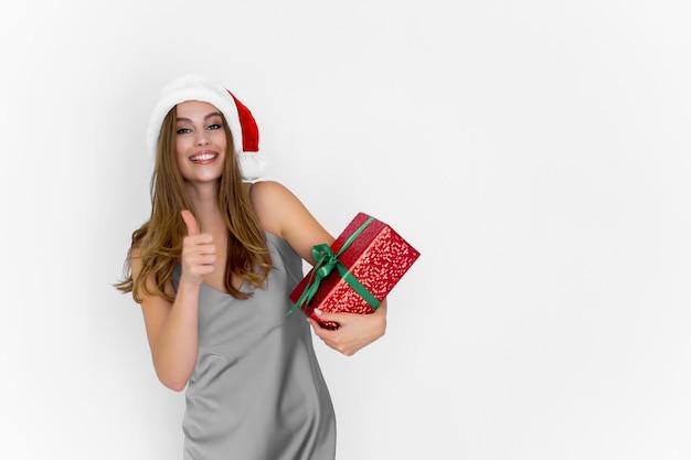 Une femme heureuse souriante et positive du père noël tient une boîte-cadeau pendant que les gestes du pouce vers le haut font une excellente célébration