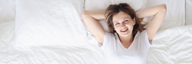 Une femme heureuse souriante se trouve sur un lit blanc, bon repos et concept de règles d'humeur positive