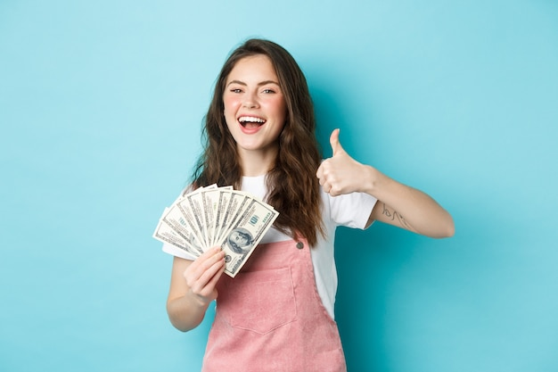 Femme heureuse souriante tenant de l'argent, des billets d'un dollar et montrant le pouce vers le haut, recommandant un prêt d'argent rapide et l'air satisfait, debout sur fond bleu