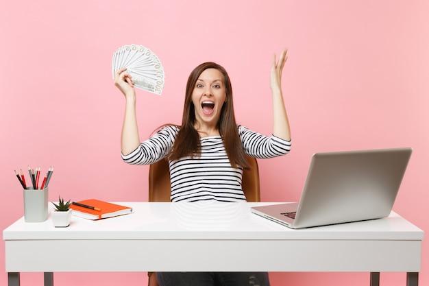 Femme heureuse surprise écartant les mains tenant un paquet de dollars, argent comptant travaillant au bureau au bureau blanc avec ordinateur portable pc