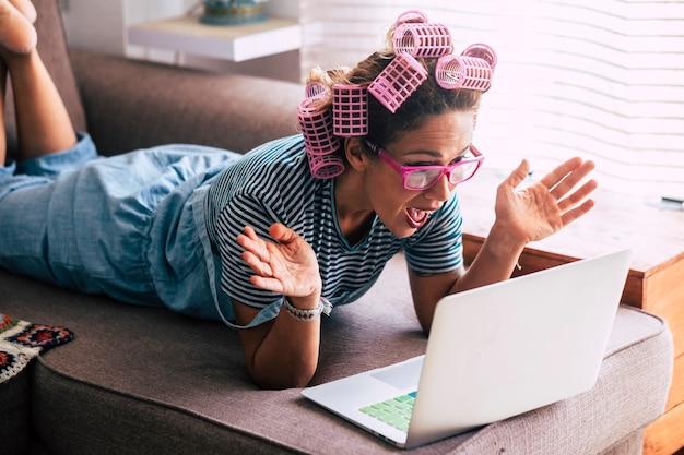 Femme heureuse surprise et excitée à la maison à la recherche d'un ordinateur portable assis sur le canapé - soins capillaires de beauté fre femmes - réception d'e-mails de notification de nouvelles et de bonheur