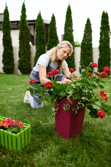 Femme heureuse en tablier travaille avec des fleurs dans le jardin