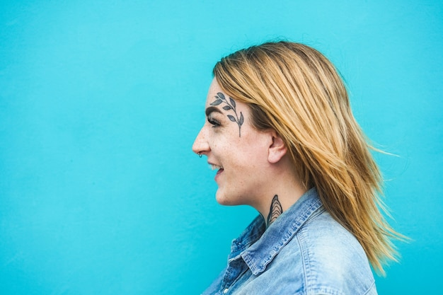 Femme heureuse avec des tatouages sur son visage