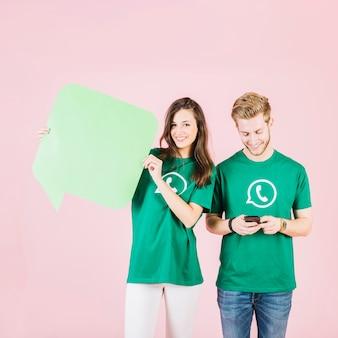 Femme heureuse tenant la bulle de dialogue à côté de l'homme à l'aide de smartphone