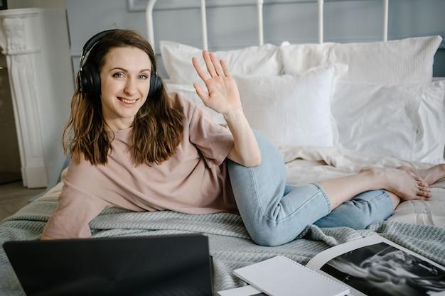 Femme heureuse en tenue décontractée avec les écouteurs travaillant sur un ordinateur portable à distance de la maison sur le lit