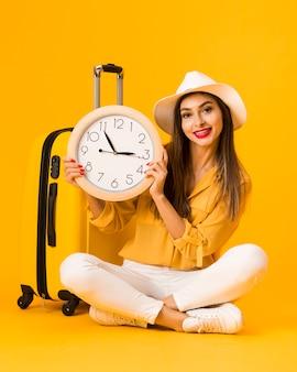 Femme heureuse, tenue, horloge, côté, bagage