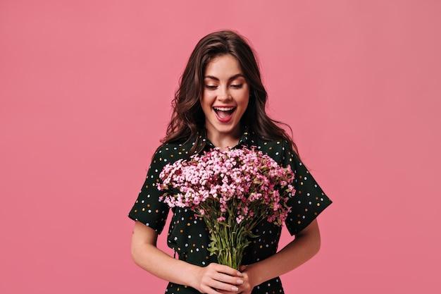 Une femme heureuse en tenue à pois tient un bouquet sur un mur rose
