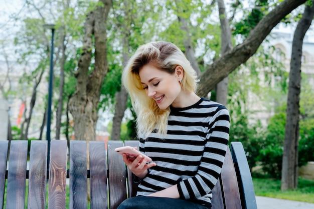 Femme heureuse textos sur un smartphone portant un haut rayé et assis en plein air sur un banc