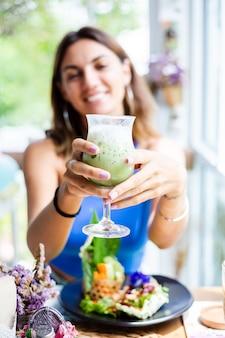 Femme heureuse tient du thé vert matcha japonais avec de la glace en verre au café femme avec une boisson antioxydante saine en été café mignon
