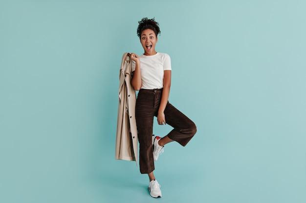 Femme heureuse avec trench-coat debout sur une jambe