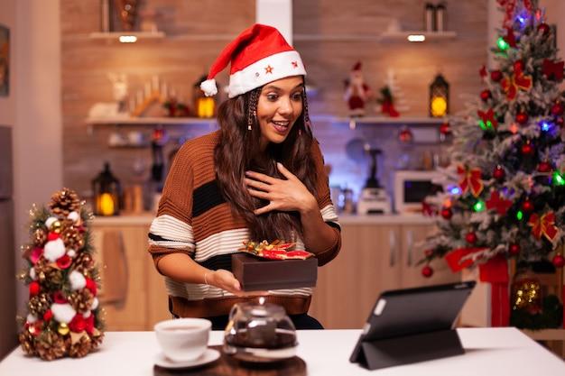 Femme heureuse utilisant l'application de conférence vidéo sur tablette