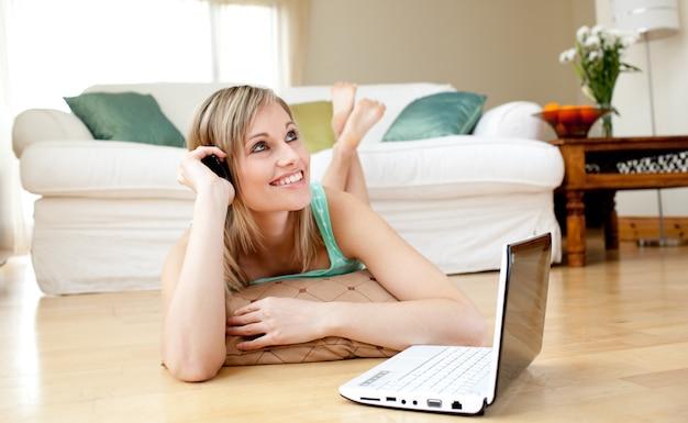 Femme heureuse, utilisation, a, laptopp, mensonge, plancher