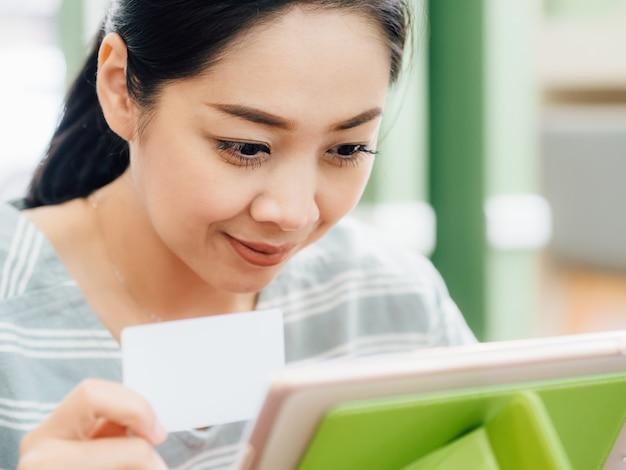 Femme heureuse utilise une carte de crédit maquette blanche pour faire des achats en ligne sur tablette.