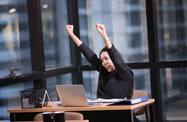 Une femme heureuse utilise un ordinateur portable pour travailler