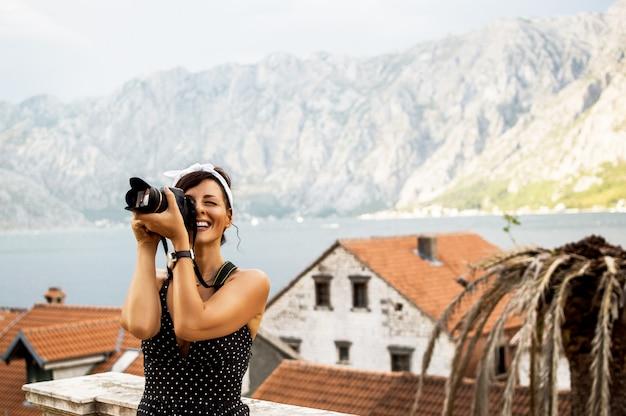 Femme heureuse en vacances photographier avec un reflex numérique.
