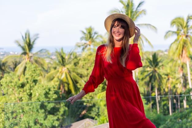 Femme heureuse en vacances en robe d'été rouge et chapeau de paille sur balcon avec vue tropicale sur mer et plam.