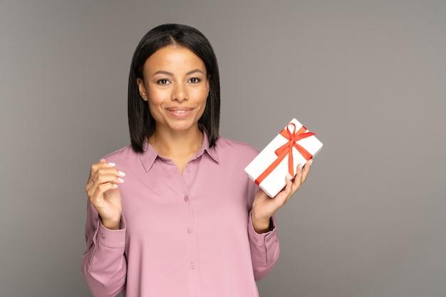 Femme heureuse de vente saisonnière avec boîte achetant des cadeaux sur la promo du vendredi noir et des offres spéciales de remise