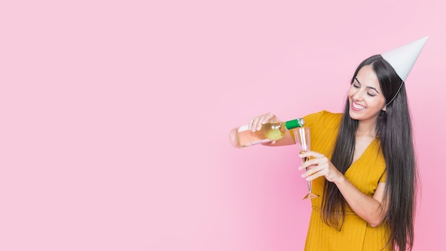 Femme heureuse, verser le vin dans le verre sur fond rose