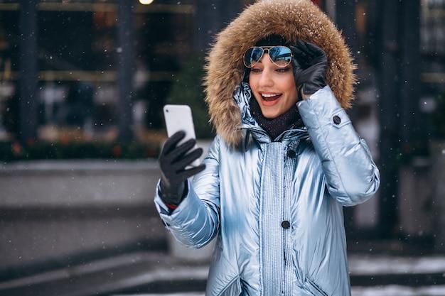 Femme heureuse en veste bleue parlant au téléphone