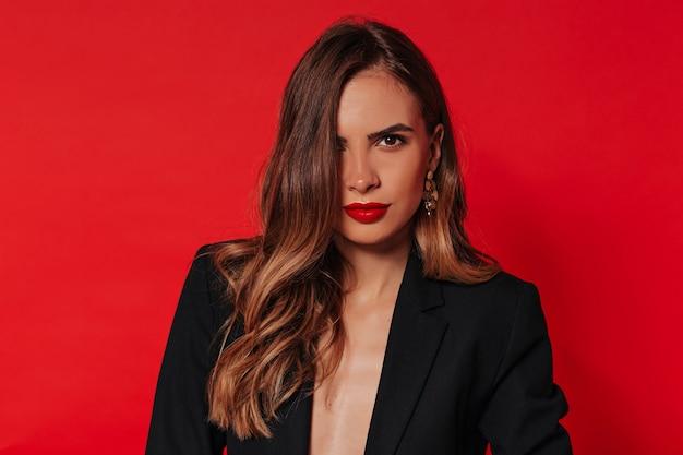 Femme heureuse en veste noire posant sur un mur rouge