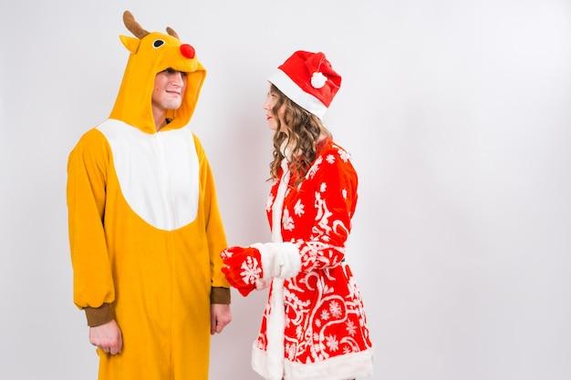 Femme heureuse en vêtements de santa avec un homme en costume de cerf sont debout sur le mur blanc