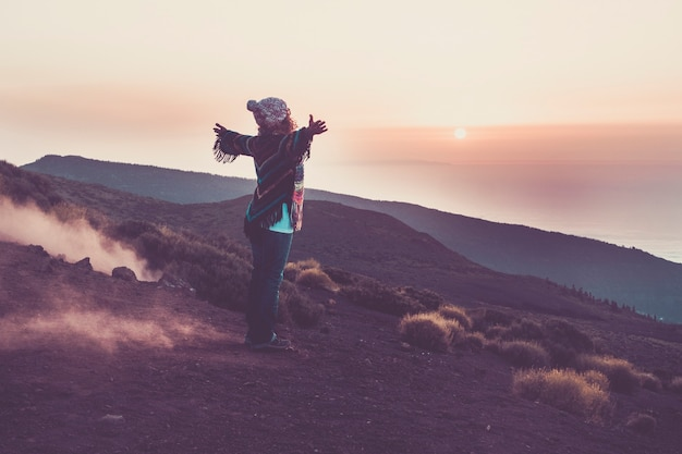 Femme heureuse de voyageur vue de l'arrière ouvrant les bras pour embrasser la merveilleuse nature impressionnante pendant l'heure du coucher du soleil