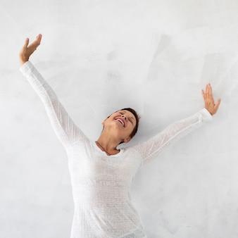 Femme heureuse vue de face, levant les mains