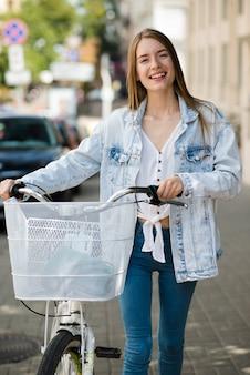 Femme heureuse vue de face avec son vélo