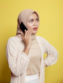 Femme hijab à l'aide d'un téléphone avec expression surprise isolée sur mur jaune