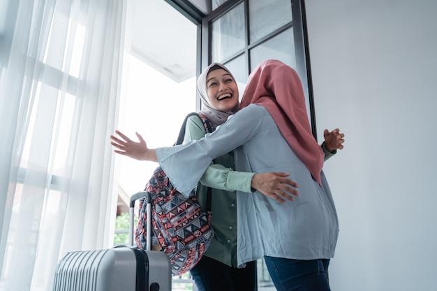 Une femme hijab embrasse sa sœur lorsqu'elle se rencontre à la porte de la maison