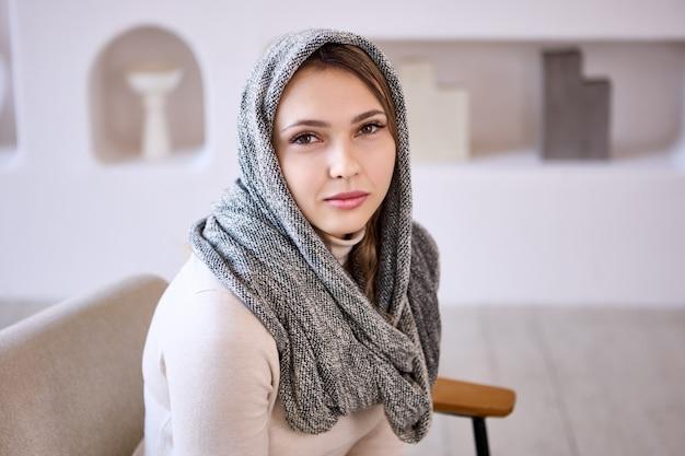 Une femme en hijab est assise dans un salon