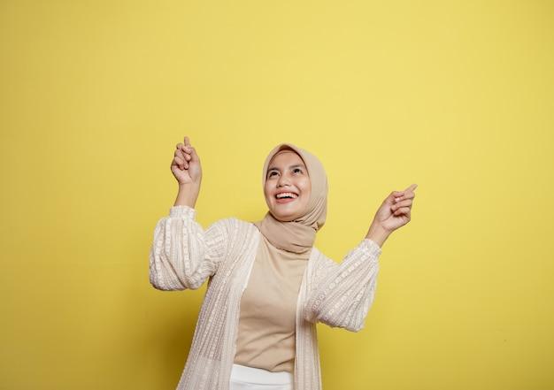 Femme hijab pointant un espace vide isolé sur un mur jaune