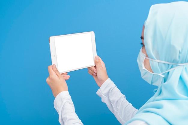 Femme avec hijab portant un masque chirurgical à l'aide de tablette
