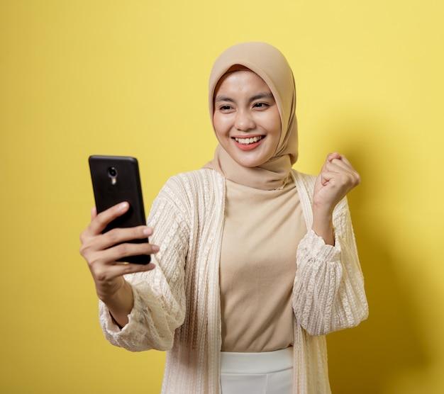 Femme hijab sur un téléphone d'appel vidéo avec expression heureuse isolé sur mur jaune