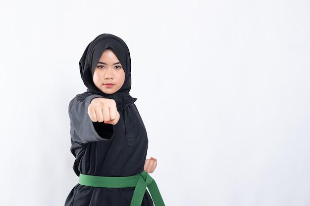 Femme en hijab en uniforme de pencak silat pose frapper avant