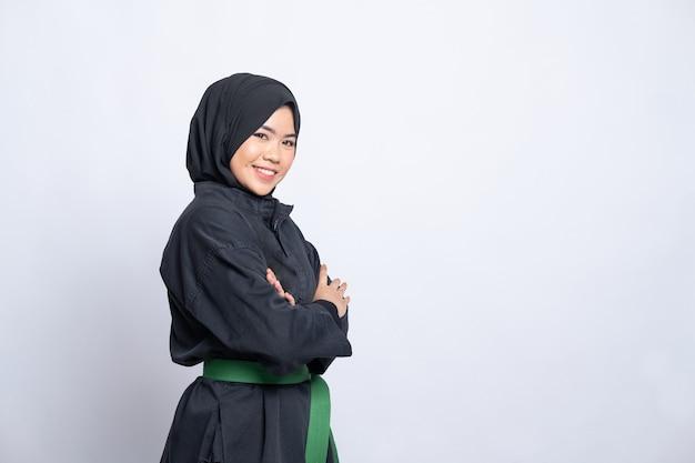 Femme en hijab en uniforme de pencak silat pose les mains croisées