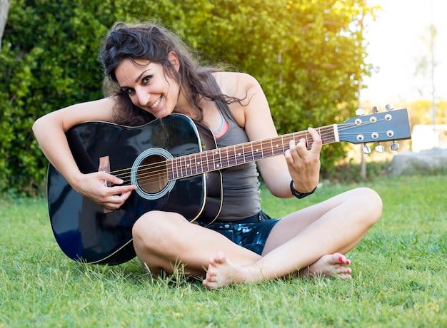 Femme hippie jouant de la guitare sur l'herbe en été