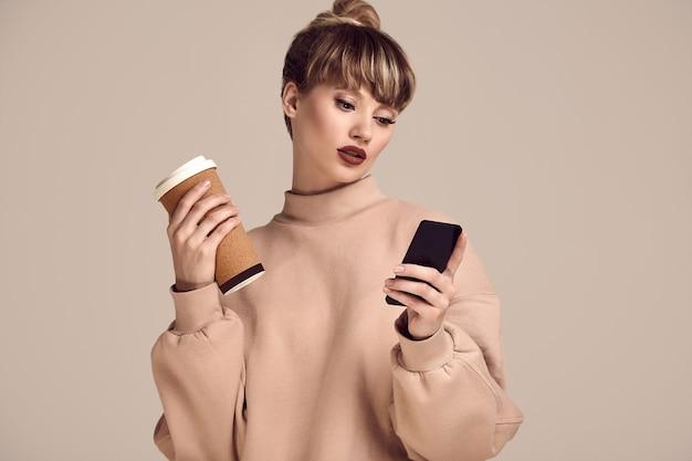 Femme hipster blonde belle glamour avec une tasse de café et téléphone