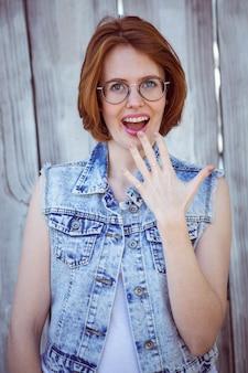 Femme hipster choquée souriant à la caméra,