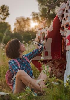 Une femme hipster en forme de chaman recherche l'inspiration de la terre mère dans un wigwam dans la nature.
