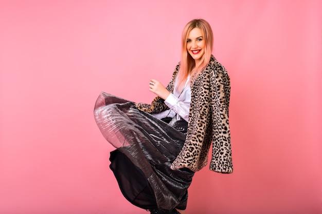 Femme de hipster heureux dansant et s'amusant à fond de studio rose, portant une tenue de cocktail de fête et un manteau léopard de fourrure, temps de vacances d'hiver.
